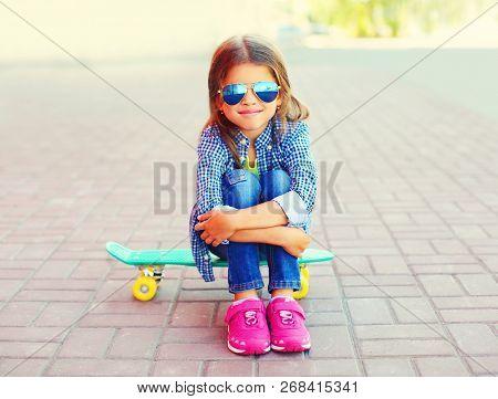 Stylish Portrait Happy Smiling Little Girl Sitting On Skateboard On City Street