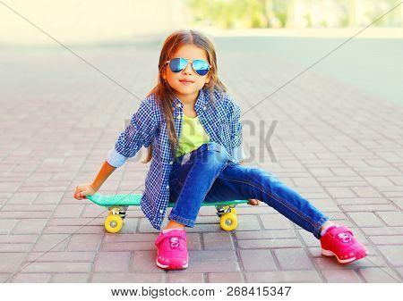 Stylish Portrait Smiling Little Girl Sitting On Skateboard On City Street