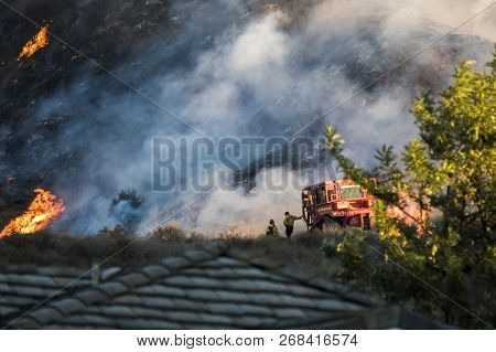 Two Firefighters Stand Next To Bulldozer With Hillside On Fire In Background During California Wools