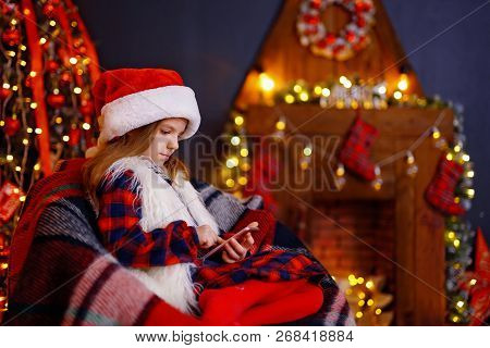 Happy Little Girl In Santa Hat, Plaid Dress With Fur Playing With Her Smart Phone While Sitting On A