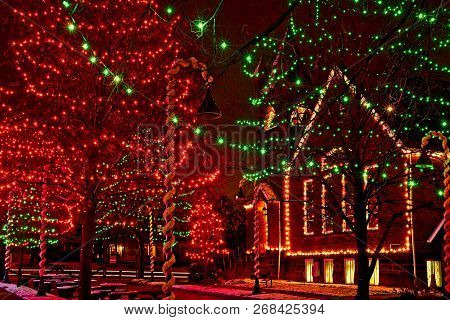 A Small-town Church And Village Square Trees Are Lit Up For Christmas