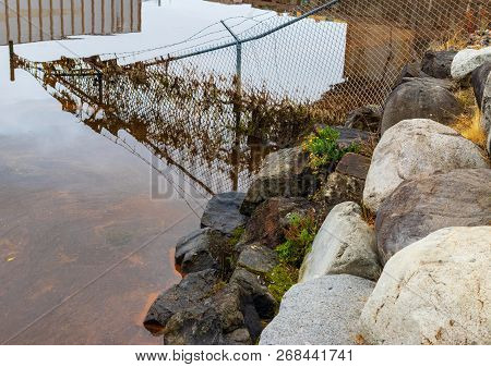 Fence Submerged In Tidal Water With Grass And Debris By A Rocky Shore