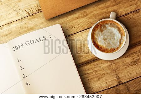 List For 2019 Goals In The Book With Coffee On Wooden Table. Goals Of 2019. Happy New Year 2019