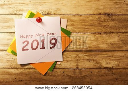 Happy New Year 2019 Written In Notes On Wooden Wall Background. Happy New Year 2019