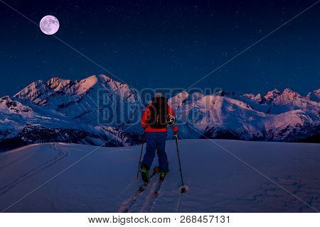 Night ski with amazing view of swiss famous mountains in beautiful winter snow. The skituring, backcountry skiing in fresh powder snow.