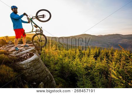 Mountain biker riding on bike in spring mountains forest landscape. Man cycling MTB enduro flow trail track. Outdoor sport activity.