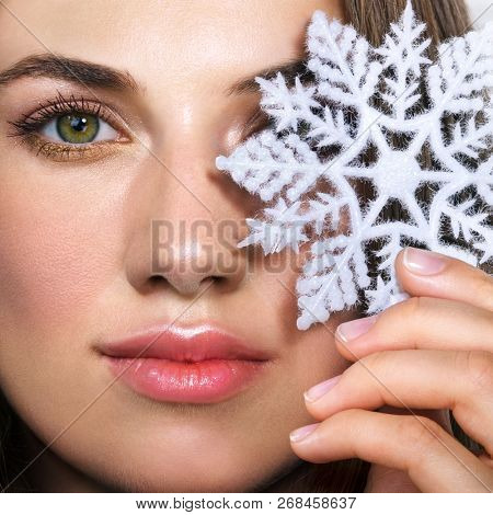 Beautiful young woman and snowflake. New year holiday concept.