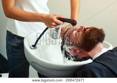 Hairdresser Washing Hair To Her Handsome Client. Barber Washing Head Client. Hairstylist Washing Cli