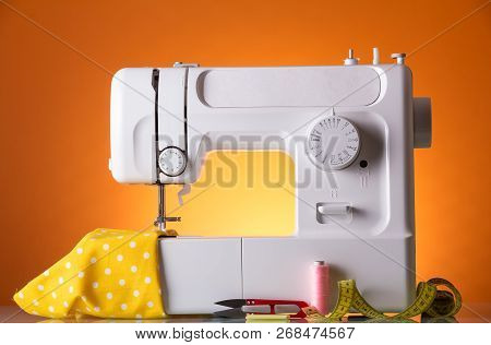 White Electric Sewing Machine In The Workplace Of A Seamstress
