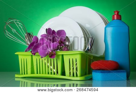 Clean Dishes And Cutlery In The Dryer On A Green Background Decorated With A Branch Of Orchids