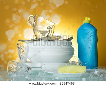 Clean Dishes And Cups, Dishwashing Detergent And Sponge On A Yellow Background In Soap Bubbles