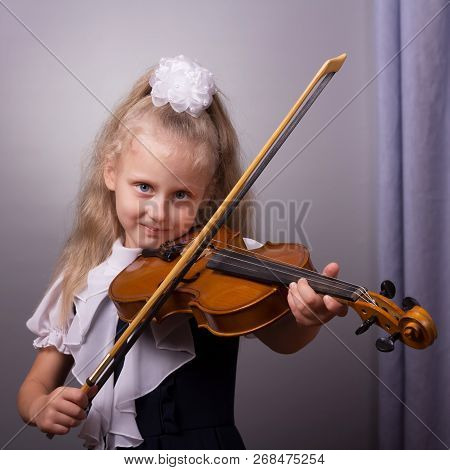 Beautiful Little Girl Playing The Violin On Bright Gray Background