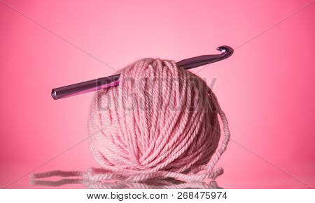 Bright Pink Ball Of Wool And A Crochet Hook On A Pink Background