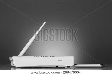 White Router And A Smartphone On A Bright Beautiful Gray Background