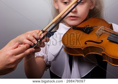 Class Study Of Playing The Violin. The Little Girl Teacher Is Correcting The Hand With A Bow