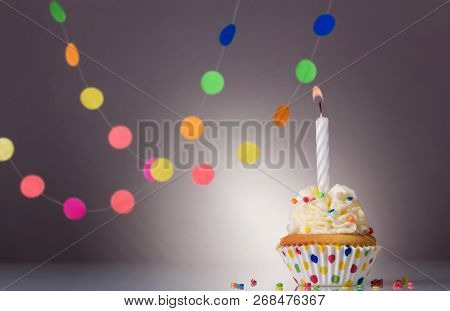 Festive Cupcake With Candle On Grey Background With Colourful Garland