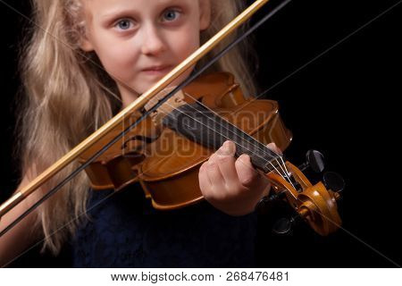 Little Blonde Girl Playing The Violin Isolated On A Black Background