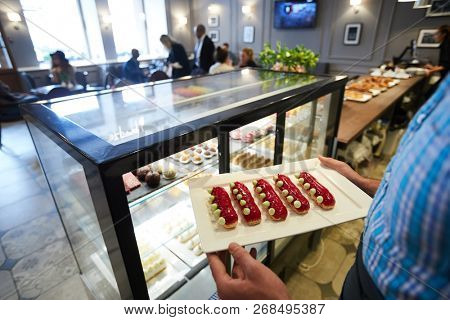 Cafeteria clerk carrying tray with group of tasty eclairs glazed with confiture