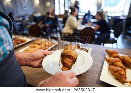 Cafeteria clerk putting fresh puff croissant on plate while serving one of clients