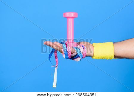 Male Hand With Bandage Hold Measuring Tapes And Dumbbell. Sport Equipment Concept. Equipment For Fit
