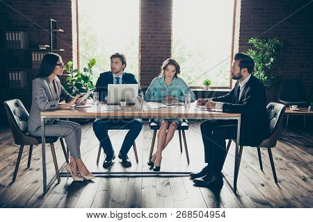 Group of calm professional banker broker economist employee employer sit behind wooden table discuss offer from main office indoor loft interior poster