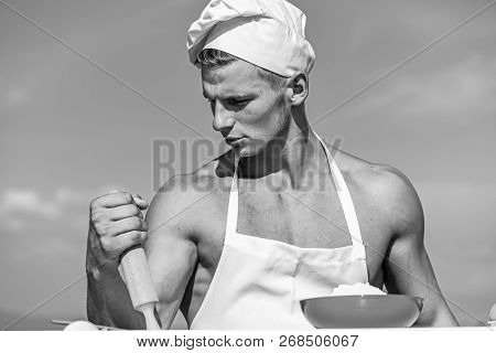 Man On Confident Face Wears Cooking Hat And Apron, Sky On Background. Cookery Concept. Cook Or Chef