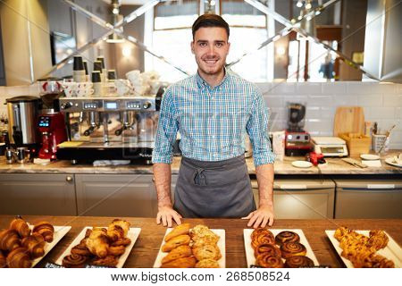 Young bakery clerk in apron standing by counter with large assortment of fresh pastry