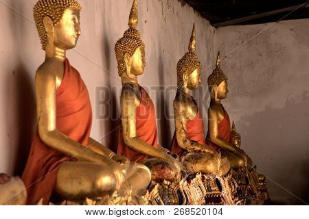 Close up shiny golden buddha statues in a row with beam of light in buddhist temple in Damnoen Saduak, Floating Market near Bangkok, Thailand