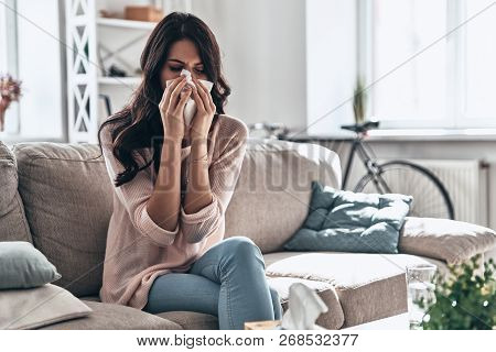 Cold And Flu. Sick Young Woman Blowing The Nose Using Tissue Paper While Sitting On The Sofa At Home