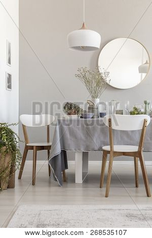 Lamp Above White Chairs And Table In Grey Dining Room Interior With Plants And Round Mirror. Real Ph