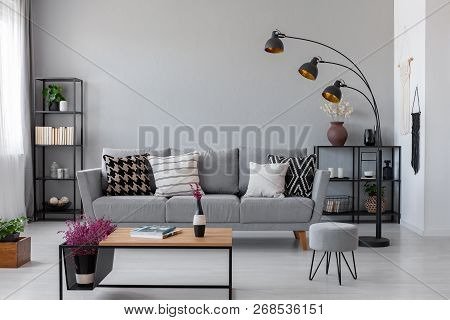 Copy Space On The Real Photo Of Industrial Living Room With Dark Metal Furniture And Grey Couch With