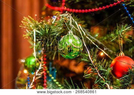 Tinsel And Toys, Balls And Other Decorations On The Christmas Christmas Tree Standing In The Open Ai