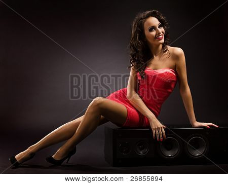 Girl in red dress sitting on Big Audio Stage Speaker.