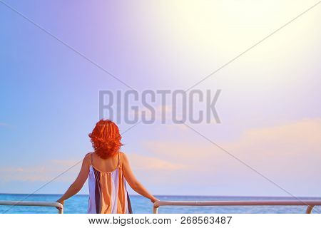 Behind Girl On Pier. Woman Standing On The Pier At The Railing At Sunrise.