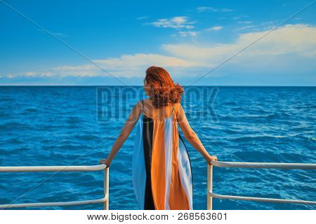Behind Girl On Pier. Woman In Colorfull Dress Standing On The Pier.