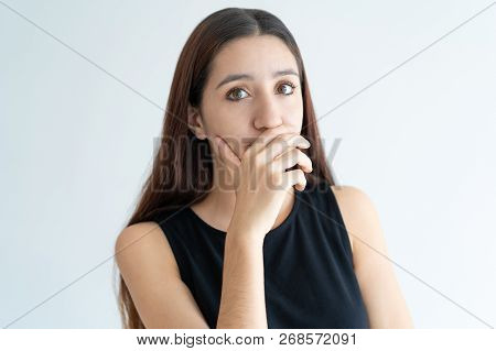 Portrait of laughing young woman covering mouth with hand. Face of Asian girl confused with bad odor. Shyness concept poster