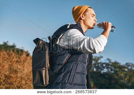 Young Stylish Tourist Blogger Is Drinking Water While Walking At The Mountains