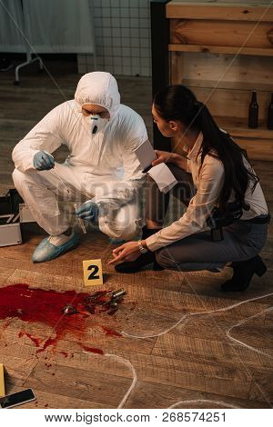 Forensic Investigator And Concentarted Female Detective Taking Notes And Investigating Crime Scene T