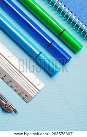 Markers, Compasses, Rulers And Notebooks On A Blue Background