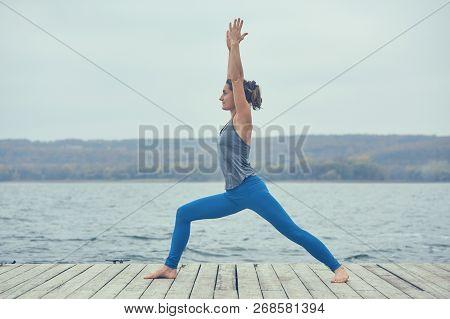 Beautiful Young Woman Practices Yoga Asana Virabhadrasana 1 - Warrior Pose 1 On The Wooden Deck Near