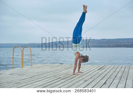 Beautiful Young Woman Practices Handstand Yoga Asana Adho Mukha Vrikshasana - Downward Facing Tree P