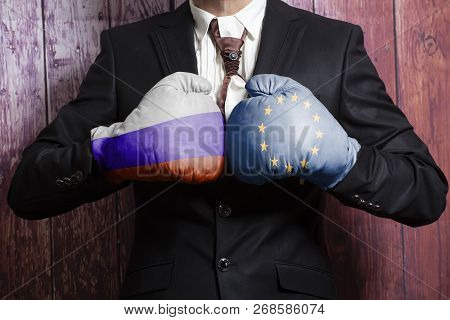 Businessman In Boxing Gloves With Russian And European Union Flag. Russia Versus European Union Conc