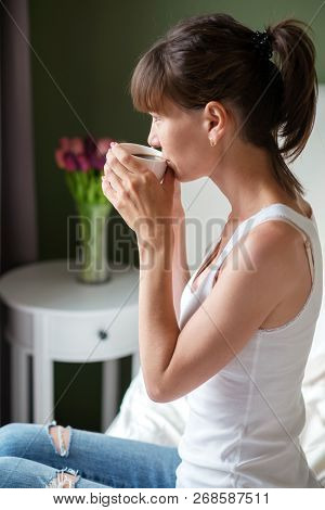 Young Woman Sitting On The Bed, Holding A White Cup And Looking Out The Window
