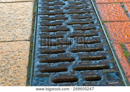 Drainage Paved With Red And Yellow Tile, Drainage On The Sidewalk, The Grille Is A Rain Gutter On Th