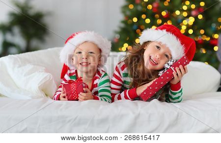 Happy Children  In Pajamas  With Gifts On Christmas Morning Near Christmas Tree