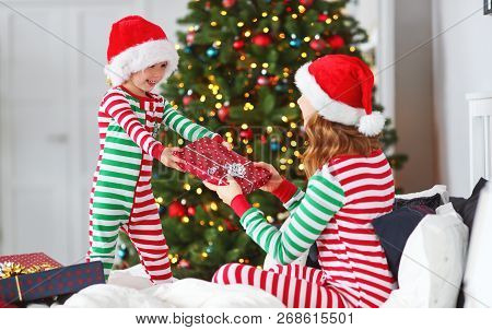 Happy Family Mother Hug Her Baby Son  In Pajamas  Opening Gifts On Christmas Morning Near Christmas