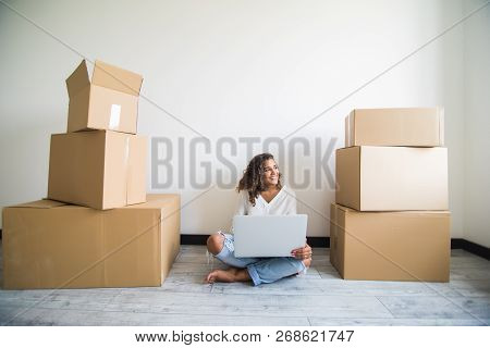 Happy Young Woman Sitting On Floor Near Moving Boxes. Young Woman Moving To New Home. Woman Using La