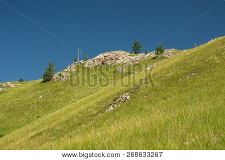 Minimalist Hill Covered With Rich Greenery. Background From Picturesque Rocky Terrain On Top Of Moun