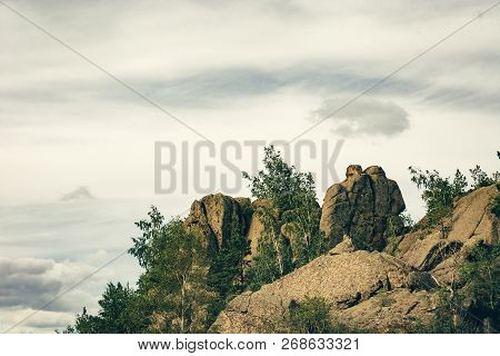 Beautiful Stones In Form Of Two People On Top Of Mountain Surrounded By Greenery. Rainy Cloud In For