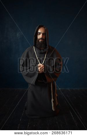 Monk in black robe with hood kneeling and praying